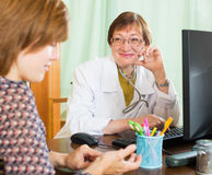 Mature doctor behind computer with patient Royalty Free Stock Photos