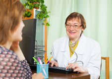 Mature doctor behind computer with patient Royalty Free Stock Image