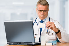 Mature doctor check some medicines. Mature doctor examining a medication's case to make prescriptions in his clinic office Royalty Free Stock Images