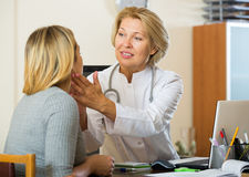 Mature doctor checking lymph nodes of female patient royalty free stock photos