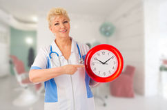Mature doctor with clock Royalty Free Stock Photos
