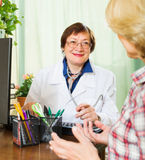 Mature doctor consulting female patient Royalty Free Stock Images
