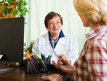 Mature doctor consulting female patient Stock Photography