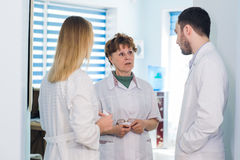 Mature doctor discussing with nurses in a hallway hospital. Doctor discussing patient case status with his medical staff Stock Photos