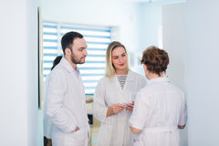 Mature doctor discussing with nurses in a hallway hospital. Doctor discussing patient case status with his medical staff Stock Photo