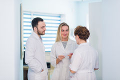 Mature doctor discussing with nurses in a hallway hospital. Doctor discussing patient case status with his medical staff Royalty Free Stock Photos