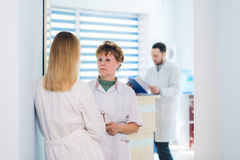 Mature doctor discussing with nurses in a hallway hospital. Doctor discussing patient case status with his medical staff Royalty Free Stock Image