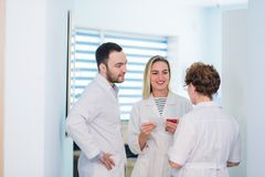 Mature doctor discussing with nurses in a hallway hospital. Doctor discussing patient case status with his medical staff. After operation Stock Image
