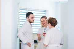 Mature doctor discussing with nurses in a hallway hospital. Doctor discussing patient case status with his medical staff Stock Images