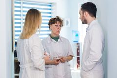 Mature doctor discussing with nurses in a hallway hospital. Doctor discussing patient case status with his medical staff Stock Image