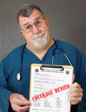 Mature Doctor Displays Coverage Denied. A doctor or nurse shows a medical form with the words COVERAGE DENIED written across it Royalty Free Stock Image