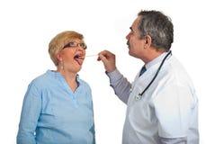 Mature doctor examine sore throat Stock Image
