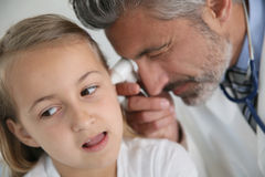 Mature doctor examining girl's ears Royalty Free Stock Photos