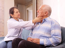 Mature doctor examining senior man Stock Photo