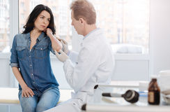 Mature doctor examining skin of the patient in the clinic Stock Images