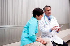 Mature doctor with female patient stock photo