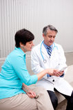 Mature doctor with female patient royalty free stock photo