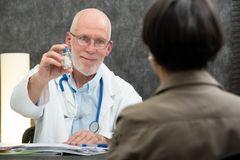 Mature doctor giving pills at his patient royalty free stock photography
