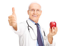 Mature doctor holding apple and giving thumb up Stock Photo
