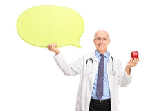 Mature doctor holding an apple and a speech bubble Royalty Free Stock Photo