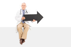 Mature doctor holding an arrow and sitting on a panel Royalty Free Stock Images