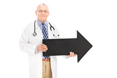 Mature doctor holding a black arrow pointing right Royalty Free Stock Images