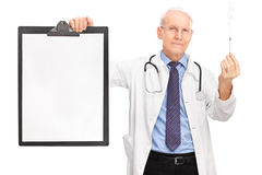 Mature doctor holding cigarette and a clipboard Stock Photography