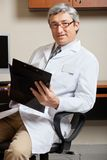 Mature Doctor Holding Clipboard Stock Photos