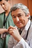 Mature Doctor Holding Glasses royalty free stock images
