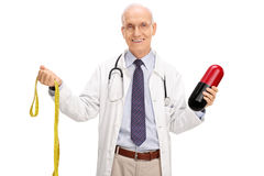Mature doctor holding a huge diet pill Royalty Free Stock Photos
