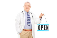 Mature doctor holding an open sign Royalty Free Stock Photography