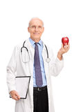 Mature doctor holding a shiny red apple Royalty Free Stock Photo