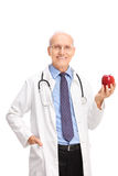 Mature doctor holding a shiny red apple Royalty Free Stock Image
