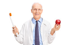 Mature doctor holding a toothbrush and an apple Stock Photo