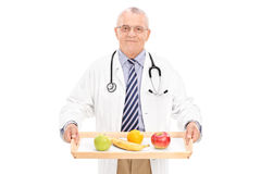 Mature doctor holding tray with a few fruits on it Royalty Free Stock Images
