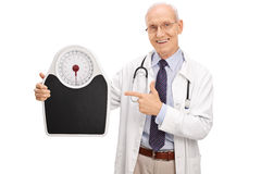 Mature doctor holding a weight scale Royalty Free Stock Photography