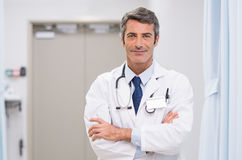 Mature doctor at hospital. Portrait of smiling doctor with stethoscope around his neck at medical clinic. Happy smiling senior doctor at hospital lobby. Mature stock photos