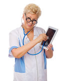 Mature doctor listen tablet PC by stethoscope Royalty Free Stock Photo