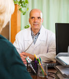 Mature  doctor listening with  female patient Stock Images