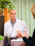Mature  doctor listening with  female patient in clinic Royalty Free Stock Photography