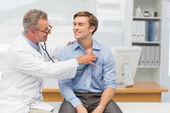 Mature doctor listening to his happy patients chest with stethoscope Royalty Free Stock Photo