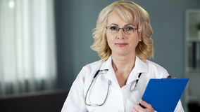 Mature doctor looking into camera guaranteeing high quality of medical services stock photos