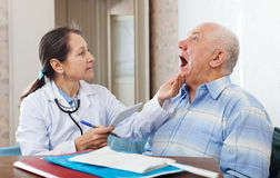 Mature doctor looks the mouth of  patient Royalty Free Stock Photos