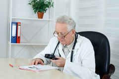 Mature doctor with loupe study a literature royalty free stock photography