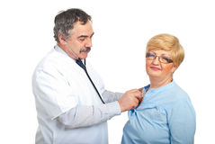 Mature doctor man examine patient woman. Mature doctor man examine  with stethoscope patient woman isolated on white background Stock Photo