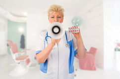Mature doctor with megaphone and pills Royalty Free Stock Images