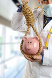 Mature Doctor with noose around a piggy bank Royalty Free Stock Photo