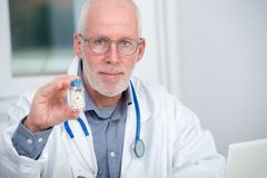 Mature doctor with pill in hospital. A mature doctor with pill in hospital Royalty Free Stock Photography