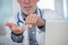 Mature doctor with pill in hospital. Mature doctor with pill in the hospital Royalty Free Stock Photo