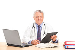 A mature doctor posing in his office Royalty Free Stock Images